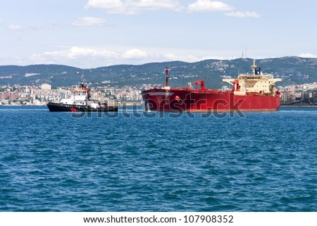 commercial cargo ship heading for port by tug boat