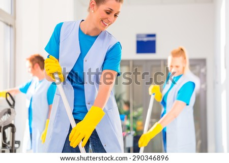 Commercial cleaning brigade working mopping the floor - stock photo