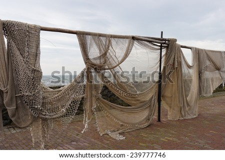 Commercial Fishing Nets Hanging out to Dry in a Small European Fishing Village - stock photo