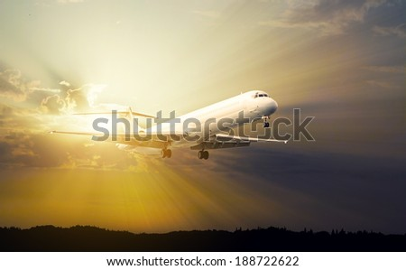 commercial jet airplane at sunset - stock photo