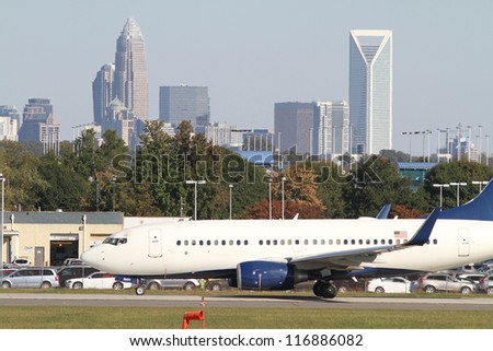 Commercial jet on an airport runway with city skyline in the background. - stock photo