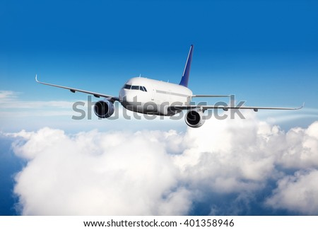 Commercial jet plane flying above clouds - stock photo