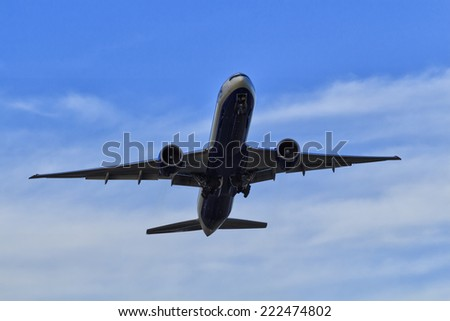 Commercial passenger airplane jet departing from airport rising altitude in blue sky with white clouds view from underneath - stock photo