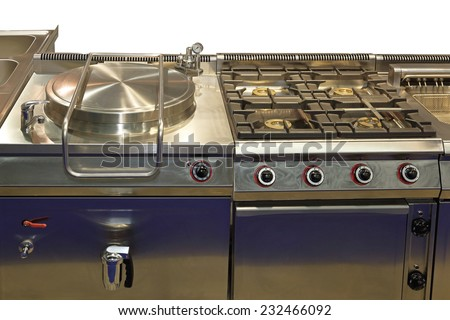 Commercial pressure cooker and big gas range in professional kitchen - stock photo