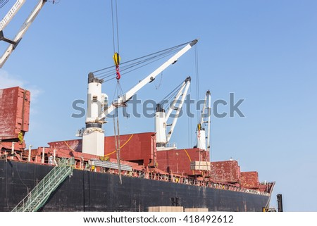 Commercial ship with cranes while unloading container to the ship at large commercial ship in harbor