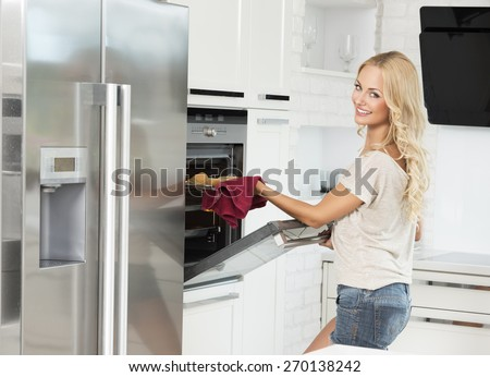 commercial shot of young girl , smiling and cooking with oven , in her luxury kitchen - stock photo