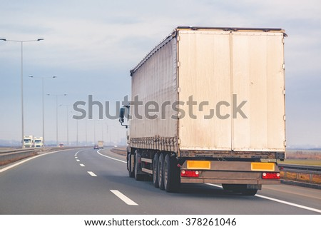 Commercial trailer truck in motion on Eastern Europe freeway on cloudy autumn afternoon, cargo transportation. - stock photo