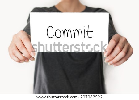 Commit. Female in black shirt showing or holding a card - stock photo