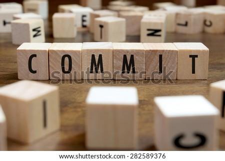 commit word written on wood block - stock photo