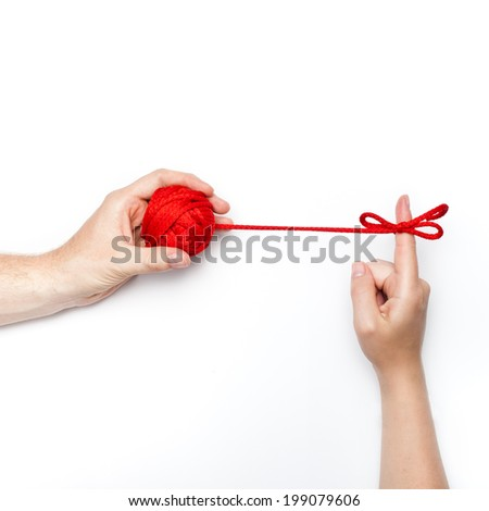 commitment and personal responsibility conceptual photo with one hand holding ball with tangled ribbon on forefinger - stock photo