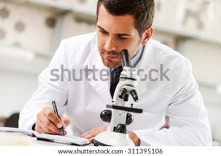 Committed to find the cure. Handsome young scientist in white uniform using microscope and writing in note pad while sitting at his working place - stock photo