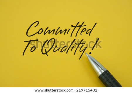 Committed To Quality! note with pen on yellow background