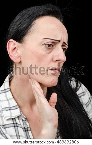 Common Cold / Flu. Woman checking for swollen glands in her neck. Black background with copy space.