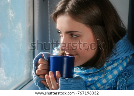 Common smiling dreaming girl in blue sweater with the cup near the frozen window in the winter