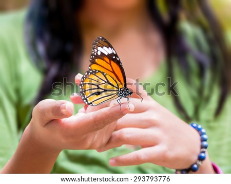 Common Tiger butterfly hanging on girl's finger, outdoor in nature