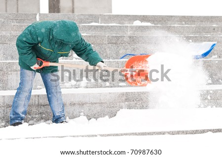 communal services worker in uniform shoveling snow in winter snowstorm - stock photo
