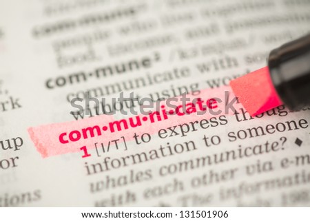 Communicate definition highlighted in red in the dictionary - stock photo