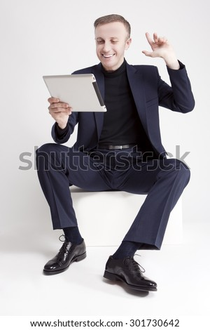 Communication and Internet Concept. Portrait of Young and Smiling Handsome Caucasian Man Using Digital Pad for Communication. Vertical Image Orientation - stock photo