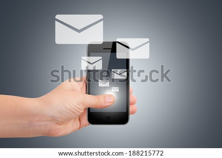Communication concept with email icons, young female hand holding smart phone on dark background. - stock photo
