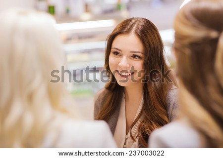 communication, friendship and people concept - happy young women meeting and talking in mall or city - stock photo