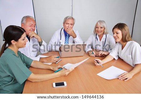 Communication in a team in a hospital with doctors and nurses - stock photo