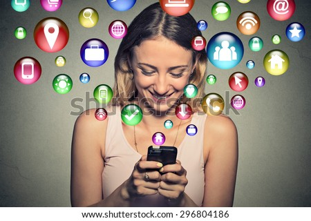 communication technology mobile high tech concept. Closeup happy young woman using texting on smartphone with social media application symbols icons flying out of screen isolated on grey background. - stock photo