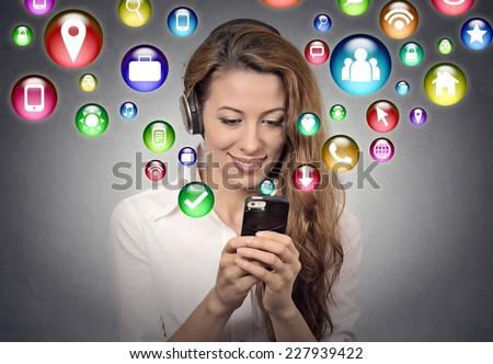 communication technology mobile high tech concept. Young woman using texting listening to music on smartphone with social media application symbols icons flying out of screen isolated grey background. - stock photo