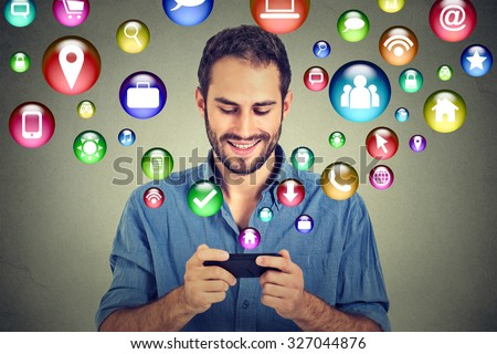 communication technology mobile phone high tech concept. Happy man using texting on smartphone social media application icons flying out of cellphone isolated grey wall background. 4g data plan - stock photo