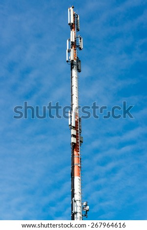 Communication tower radio mast with antenna against great blue sky - stock photo