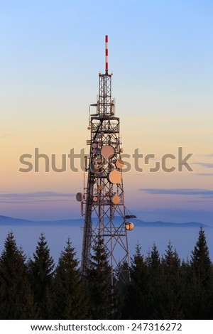 Communication Tower with Parabolic and GSM Antennas on Dusk Blue Sky, Located in The Czech Republic - Cerna Studnice - stock photo