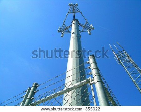 communication towers surrounded by barb wire and chain link fence - stock photo