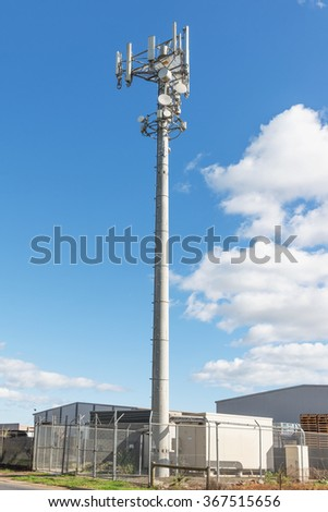 Communications Cell phone Tower against blue sky near industry buildings - stock photo