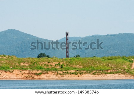 Communications tower at the shore with mountains