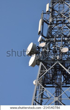 Communications tower with antennas against a blue sky  - stock photo