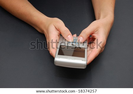 Communicator in woman hands on the black table - stock photo