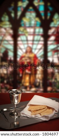 communion chalice and bread with stained glass window in the background - stock photo