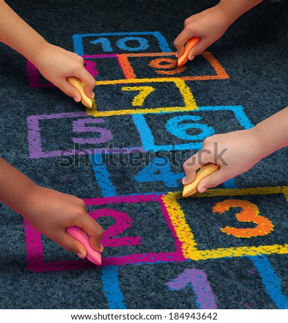 Community development education and children learning concept with a group of hands as ethnic groups of young people holding chalk cooperating together as friends to draw a playground hopscotch game. - stock photo
