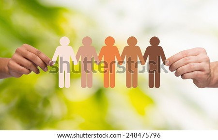 community, unity, people and support concept - couple hands holding paper chain multiracial people over green background - stock photo