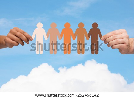 community, unity, people and support concept - couple hands holding paper chain multiracial people over blue sky and cloud background - stock photo