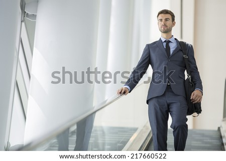 Commuter in the metro station going down the escalator - stock photo