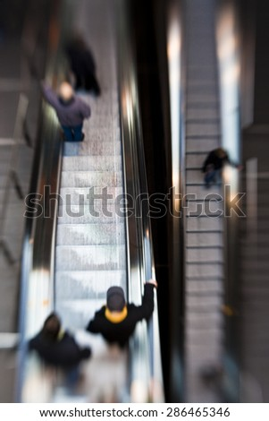 Commuters on an Escalator inside a Station or Airport - stock photo