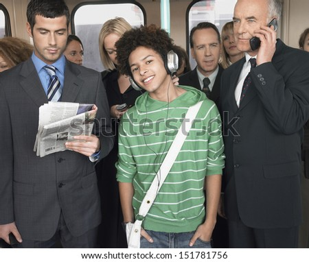 Commuters standing in train reading newspapers; talking on mobiles and listening to music - stock photo