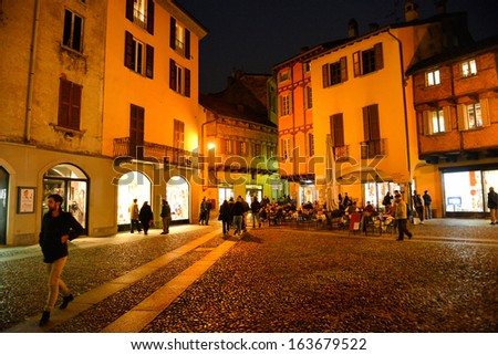 COMO, ITALY - NOVEMBER 16: People walking in the old town of Como city at the evening on November 16, 2013 in Como, Italy.