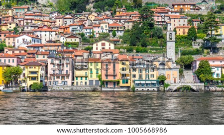 COMO LAKE, ITALY - SEPTEMBER 14: Beautiful, colorful houses of a small town on September 14, 2014 on Como Lake, Italy. Como Lake is very popular tourist attraction