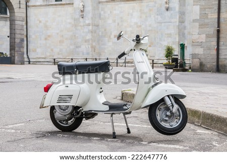 COMO MAY 15, 2014: Close up of a white shiny Vespa Piaggio parket at an empty market place representing the Italian lifestyle of a generation taken on May 15, 2014 in Como, Italy - stock photo