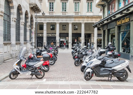 COMO MAY 15, 2014: Two lines of Italian scooters in front of an American store of the brand Foot Locker in an ancient European city taken on May 15, 2014 in Como, Italy - stock photo