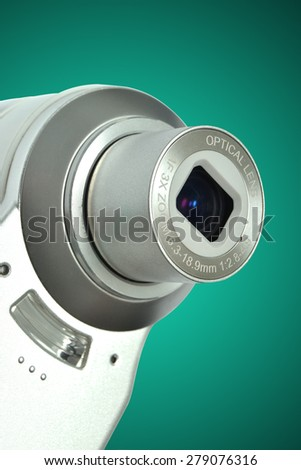 compact digital camera on green background