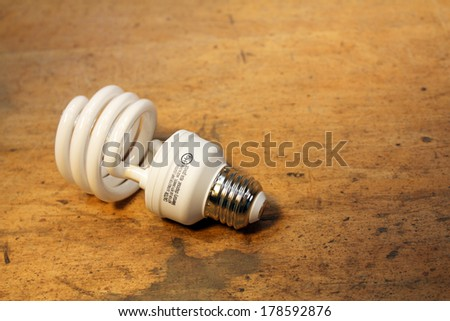 Compact fluorescent light bulb isolated over wood background - stock photo