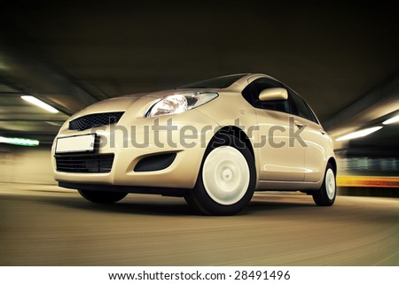 Compact hatchback driving fast in parking house - stock photo