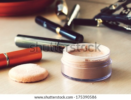 Compact pocket powder and a powder puff and other cosmetics on the table - stock photo